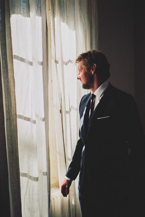 portrait d'un marié qui regarde par la fenêtre après les préparatifs par thomas biarneix photographe de mariage en argentique à Toulouse