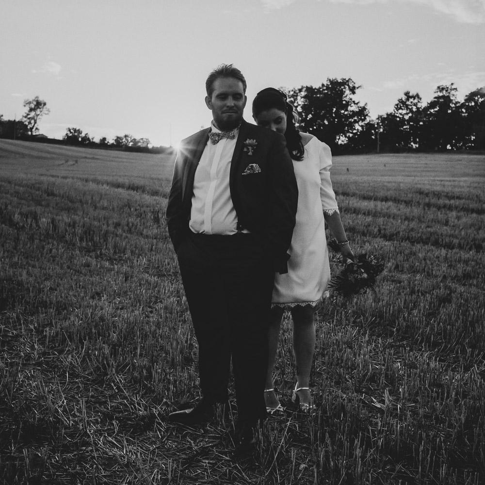 portrait de couple dans un champ au soleil couchant par thomas biarneix photographe de mariage en argentique à Toulouse